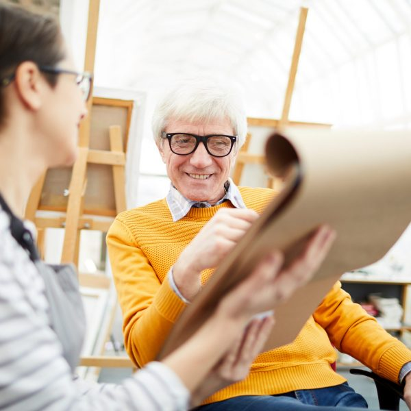 Portrait of senior art teacher working with student and smiling happily during sketch session, copy space