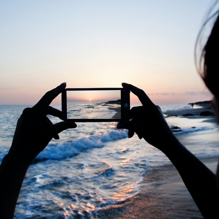 Girl is taking a sunset photo on the phone